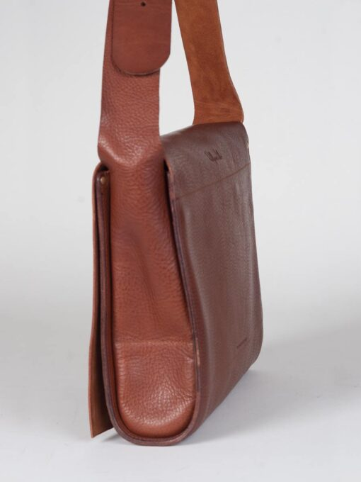 Side profile of leather messenger bag in tan